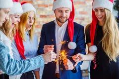 Коллеги дела на рождественской вечеринке офиса владение домашнего ключа принципиальной схемы дела золотистое достигая небо к Стоковая Фотография