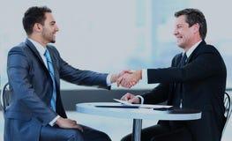 Коллеги дела сидя на таблице во время встречи при 2 мужских исполнительной власти тряся руки Стоковые Фото