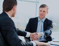 Коллеги дела сидя на таблице во время встречи при 2 мужских исполнительной власти тряся руки Стоковая Фотография