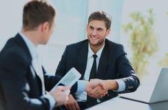 Коллеги дела сидя на таблице во время встречи при 2 мужских исполнительной власти тряся руки Стоковые Фотографии RF