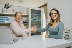 Коллеги женщины работая вместе с компьтер-книжкой в офисе жулик Стоковые Изображения RF