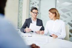 Коллеги заключая контракт на таблице в офисе Стоковые Фото