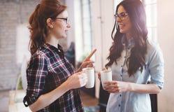 Коллеги имея перерыв на чашку кофе в современном офисе Стоковые Фотографии RF