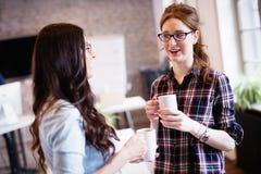 Коллеги имея перерыв на чашку кофе в современном офисе Стоковые Фото