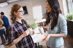 Коллеги имея перерыв на чашку кофе в современном офисе Стоковое Фото