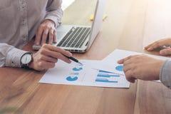 Коллеги команды 2 дела обсуждая диаграмму нового плана финансовую Стоковое Фото