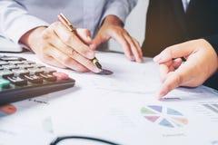 Коллеги команды 2 дела обсуждая диаграмму нового плана финансовую Стоковое Изображение