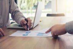 Коллеги команды 2 дела обсуждая диаграмму нового плана финансовую Стоковое фото RF