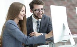 Коллеги обсуждая информацию на компьютере Стоковое Изображение