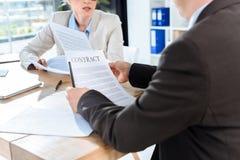 Коллеги обсуждая контракт Стоковые Фотографии RF