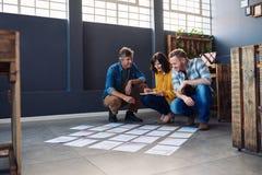 3 коллеги обсуждая обработку документов клали вне на пол офиса Стоковое фото RF