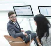 Коллеги обсуждая финансовые план-графики в рабочем месте Стоковая Фотография