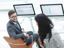 Коллеги обсуждая финансовые план-графики в рабочем месте Стоковые Фото