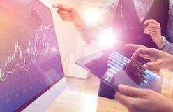 2 коллеги работая на глобальном финансовом торгуя анализе стратегии используя таблетку и компьтер-книжку Современная команда дела Стоковые Фотографии RF