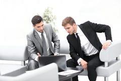 2 коллеги работая на компьтер-книжке сидя в лобби офиса Стоковая Фотография