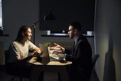 Коллеги работая последние часы в офисе обсуждая бизнес-план Стоковая Фотография RF