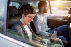 Коллеги работая совместно в заднем сиденье автомобиля Стоковые Фотографии RF