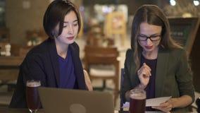 2 коллеги работая совместно в кафе используя компьтер-книжку акции видеоматериалы