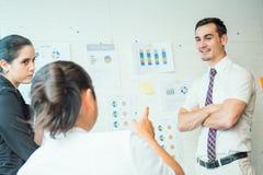 3 коллеги работы обсуждают с диаграммой стратегии Стоковые Изображения