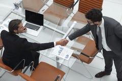 Коллеги рукопожатия около настольного компьютера Стоковое фото RF