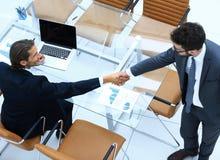 Коллеги рукопожатия около настольного компьютера Стоковые Фото