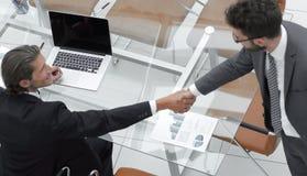 Коллеги рукопожатия около настольного компьютера Стоковое Фото