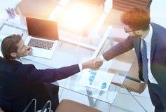 Коллеги рукопожатия около настольного компьютера Стоковая Фотография
