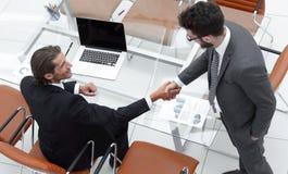 Коллеги рукопожатия около настольного компьютера Стоковое Изображение