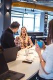 Коллеги смеясь над на встрече офиса Стоковая Фотография RF