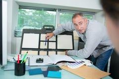 Коллеги смотря липкие примечания на борту в офисе Стоковые Изображения RF