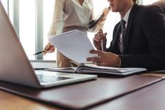 Коллеги сравнивая документы в офисе стоковое изображение