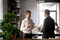 Коллеги стоя имеющ случайный разговор в офисе стоковое изображение rf