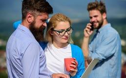 Коллеги с компьтер-книжкой работают внешний солнечный день, предпосылка природы Деловые партнеры встречая не официальную атмосфер стоковые изображения