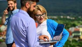 Коллеги с компьтер-книжкой работают внешний солнечный день, предпосылка природы Деловые партнеры встречая не официальную атмосфер стоковые фото