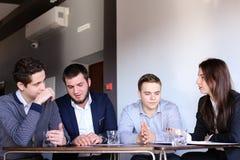 4 коллеги человека и женщины собирают для встречать на офисе  Стоковые Фотографии RF