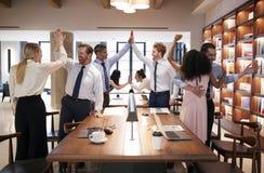 6 коллег празднуя успех в открытом офисе плана стоковое фото