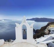 Колокольня греческой православной церков церков на водах предпосылки Эгейского моря в городке Oia на острове Santorini Стоковые Изображения