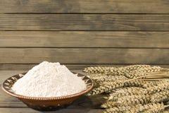 Колоски и мука пшеницы на деревянной предпосылке планки стоковое изображение