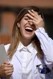 Колумбийский женский доктор Laughing Wearing Лаборатория Пальто с доской сзажимом для бумаги стоковое изображение rf