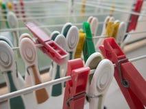 Колышки одежд на белой линии сушильщике стоковое изображение rf