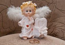 Кольца золота свадьбы и статуэтка ангела Стоковая Фотография