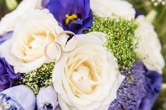 Кольца золота свадьбы лежат на букете свадьбы Стоковое фото RF