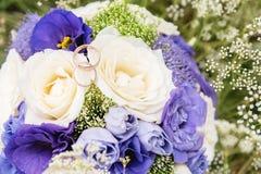 Кольца золота свадьбы лежат на букете свадьбы Стоковое Изображение