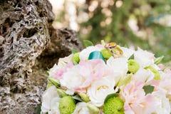 Кольца золота свадьбы лежат на букете свадьбы Стоковое Фото