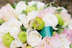 Кольца золота свадьбы лежат на букете свадьбы Стоковые Изображения RF