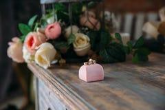 Кольца золота свадьбы на декоративной подушке с концом-вверх цветков Концепция ювелирных изделий Стоковое Изображение RF
