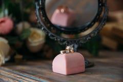 Кольца золота свадьбы на декоративной подушке с концом-вверх цветков Концепция ювелирных изделий Стоковая Фотография RF