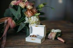 Кольца золота свадьбы на декоративной подушке с невестой цветут и холят boutonniere Концепция ювелирных изделий Стоковые Изображения RF