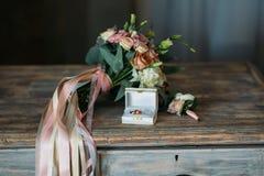 Кольца золота свадьбы на декоративной подушке с невестой цветут и холят boutonniere Концепция ювелирных изделий Стоковое Изображение RF