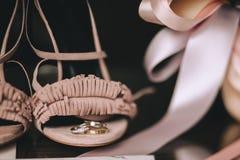 Кольца золота свадьбы с диамантами лежат на ботинках невесты пинка бархата с лентами сатинировки Конец-вверх Стоковая Фотография RF